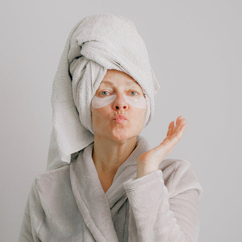 Woman wearing a towel on her hair with an eye treatment on her face.