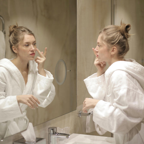 A woman applying moisturizer in the mirror while in her bathrobe.