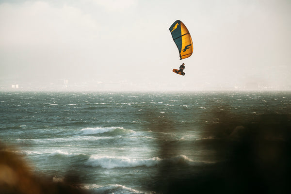 A kitesufer doing an air with the sandunes in front.