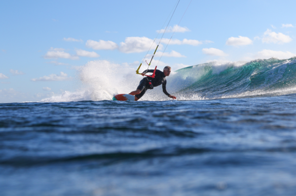 A man kitesurfing in front of breaking wave in the middle of the sea.