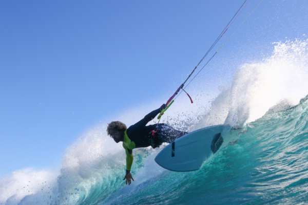 A person holding their bar with one hand slashing a wave
