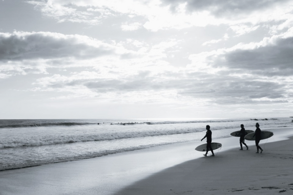 Surfers walking down the waves with their surfboards at Playa Negra.