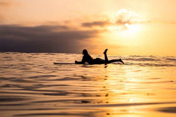 A person laying on their surfboard in the ocean as the sun sets.