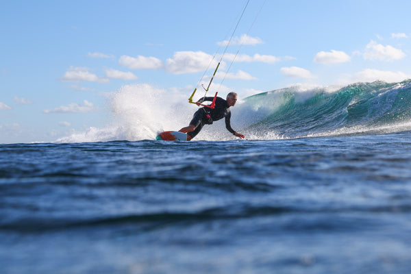 A kitesurfer on the water with F-One equipment wearing a wetsuit