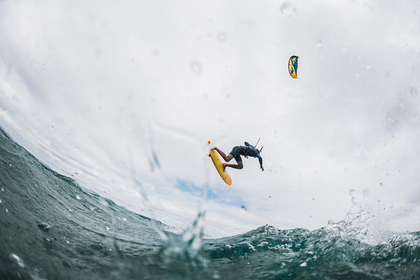 image taken from water of someone kitsurfing on yellow board