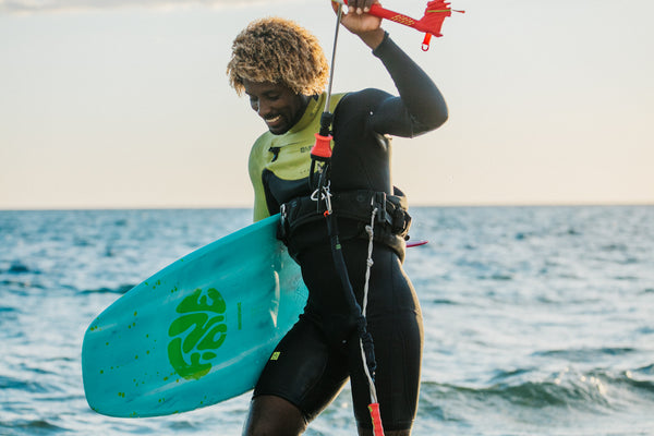 A smiling kitesurfer wearing a wetsuit and F-One equipment