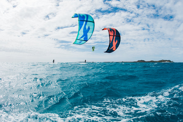 Three people kitesurfing with F-One