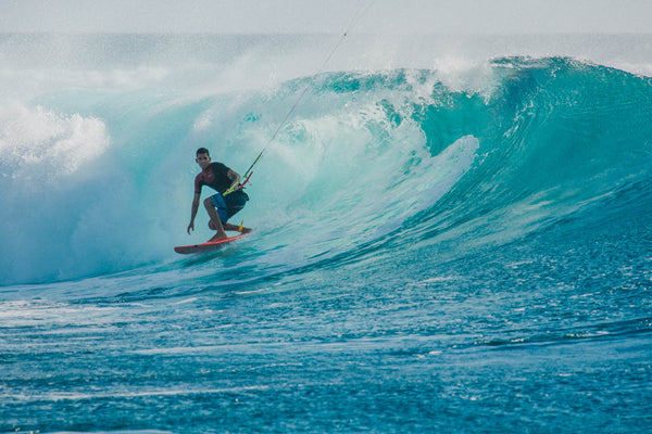 Man surfing in big, glassy blue wave