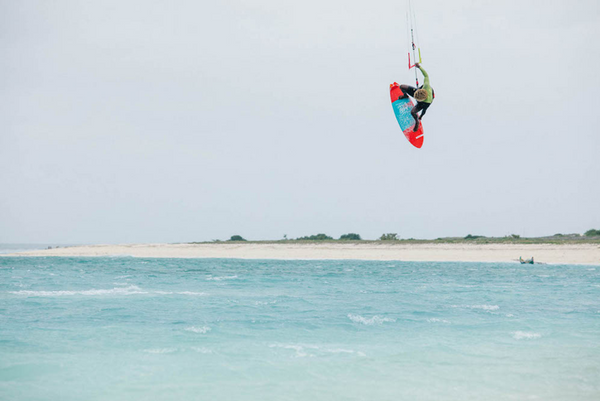 A man performing kitesurfing tricks using an F-One kiteboard