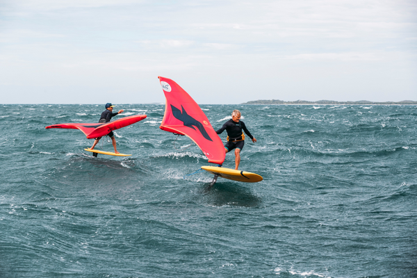 Surf riders on the water using the F-One Swing