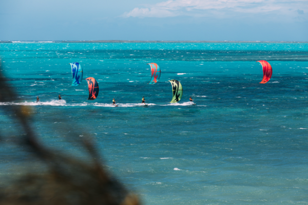 F-One kitesurfers catching some waves in a group during a winter break.
