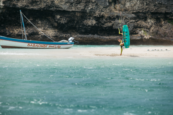 A man riding an F-One kiteboard near a boat while touching white sand.