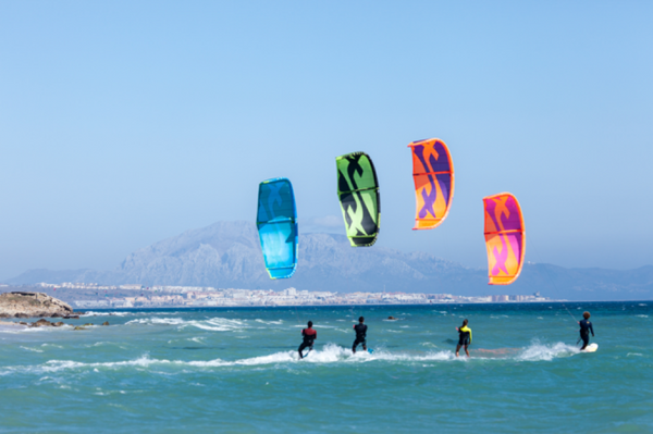 Kitesurfers out on the waves together on a sunny day