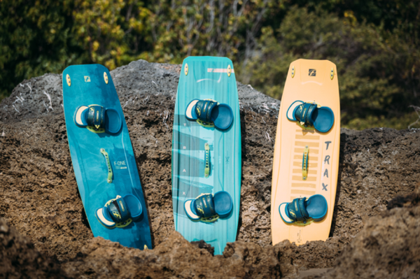 Three kitesurfing boards propped up against a rock on a beach