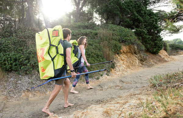 Man and woman with inflatable paddleboards on backs heading to the beach.