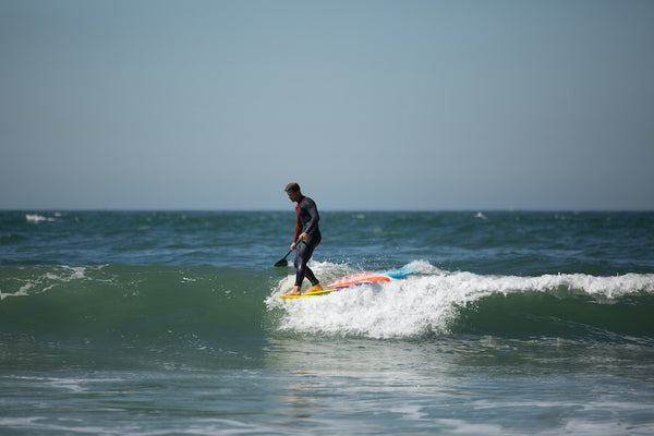 A man stood at the end of a paddleboard with paddle in hand, surfing a wave.