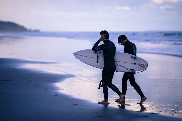 wo guys walking up the beach after enjoying a surf session together.
