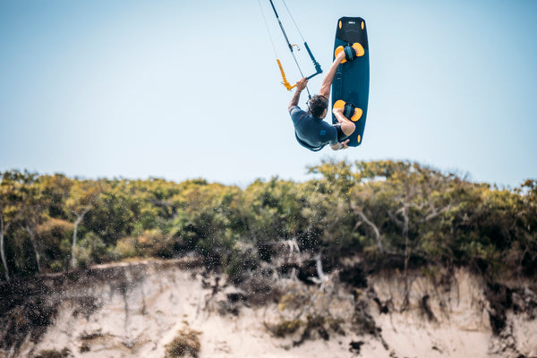 Kiteboarder in the air doing a trick in front of a sandune.