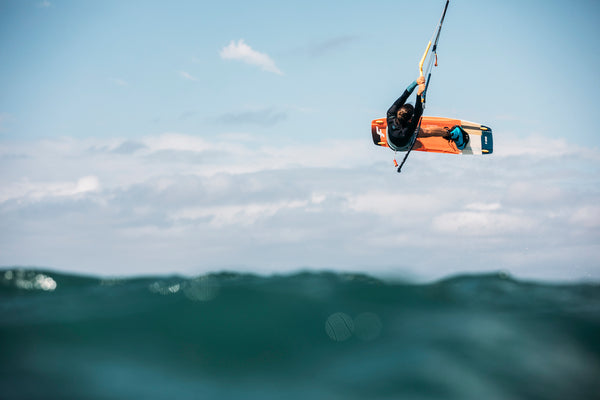 Female kitsurfer doing an air over the sea.