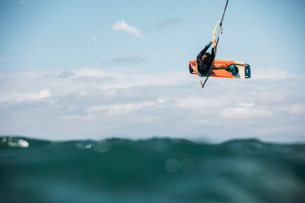 person kitesurfing in air above waves