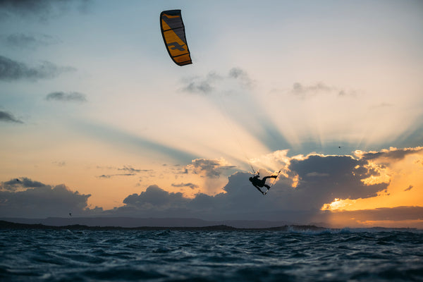 kitesurfer over ocean in sunset