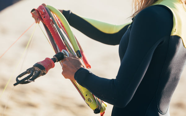 A Kitesurfer preparing their gear while wearing a wetsuit
