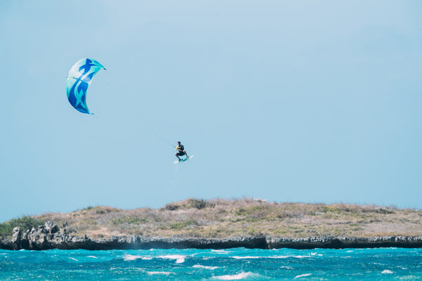 A kitesurfer with a blue kite on an ocean