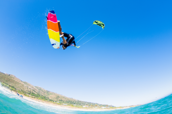 A shot taken with a waterproof camera of a kitesurfer performing a trick in mid-air.