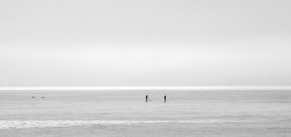 Two people paddleboarding on the calm waves at Saunton Sands.