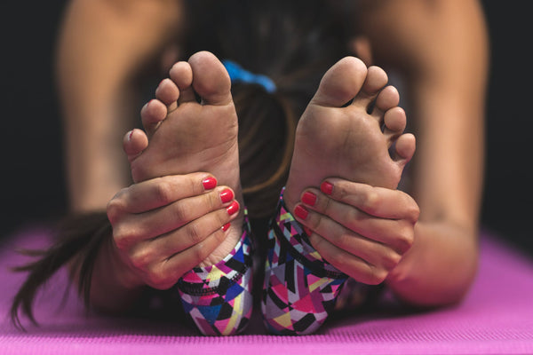 A person holding their feet as they stretch out on an exercise mat.