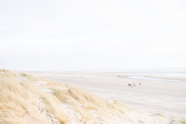 A clear view of people walking along Camber Sands beach on a bright day
