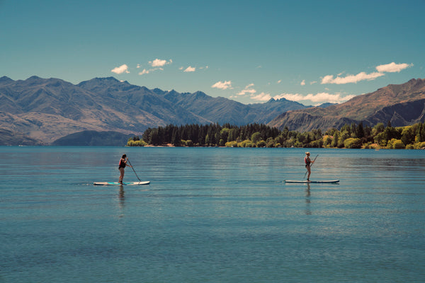 Two people SUP boarding on a flat-water lake in the sunshine.