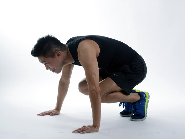 A man squatting down performing a burpee