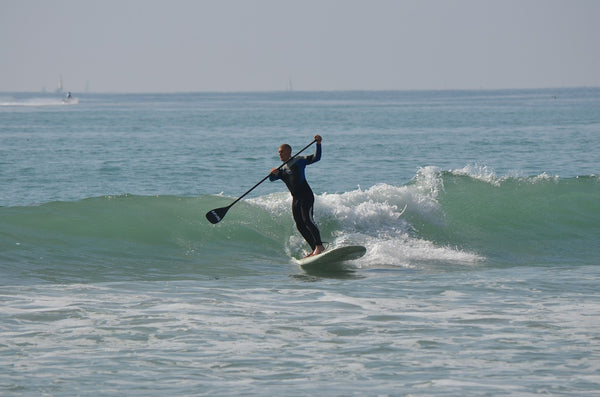A man on an inflatable SUP board riding a wave towards the shore.
