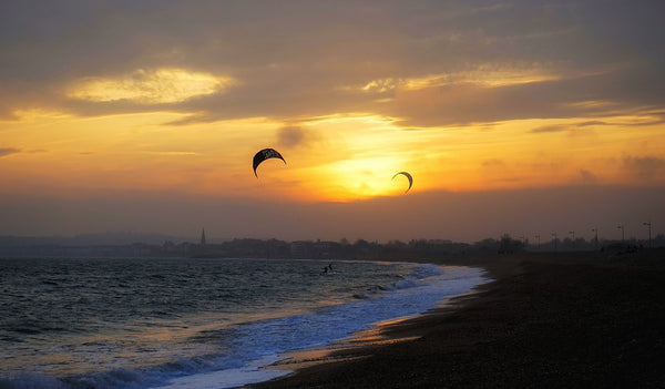 Kitesurfers on Weymouth beach surfing the waves at sunset