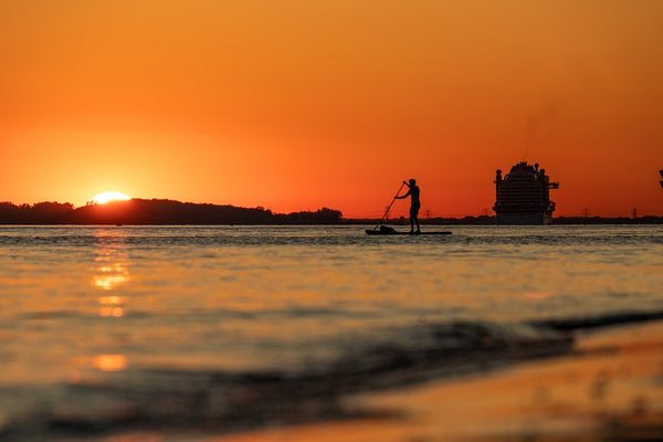 A paddleboarder in the orange sunset