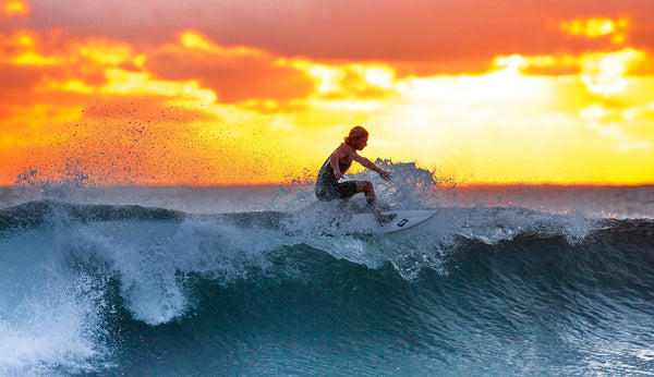A surfer catching a wave at sunset.