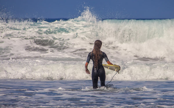 A woman wading into the sea with her surfboard to ride a wave.