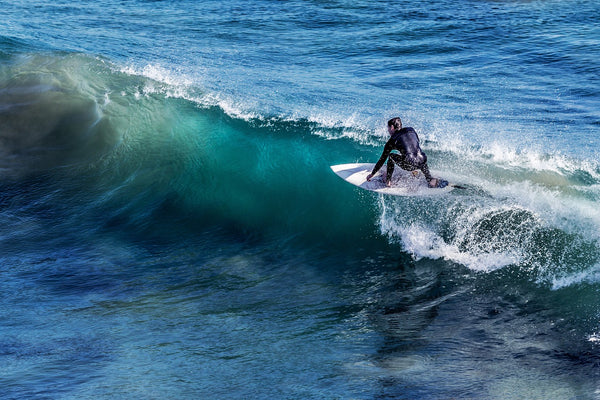 A surfer crouched down on his board riding a smaller wave.