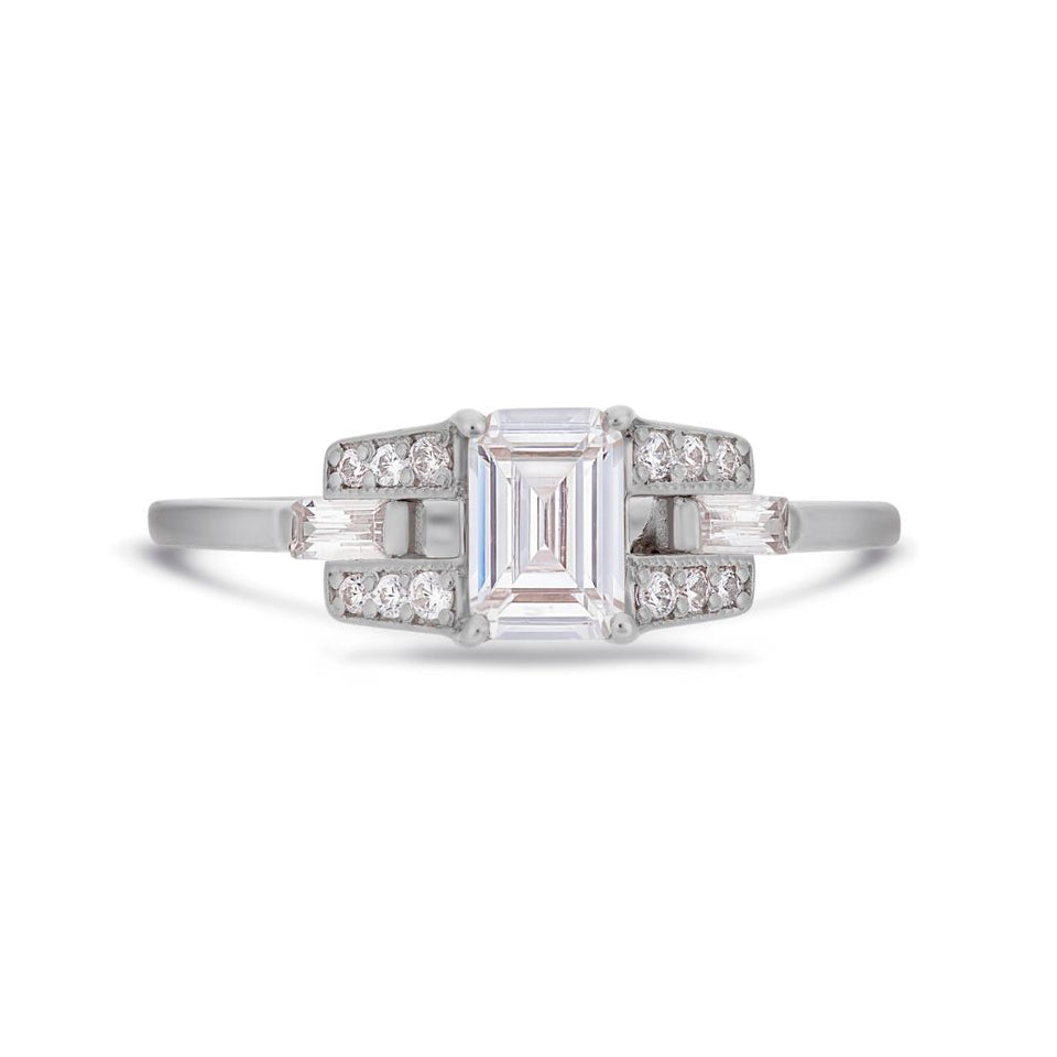 Emerald cut diamond buckle ring in platinum