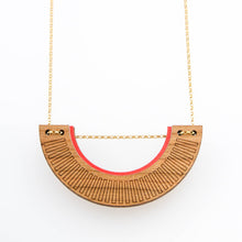 U-shaped gold chain necklace made of cherry wood, with band of red along top and chain running through the piece at the top of the U shape.