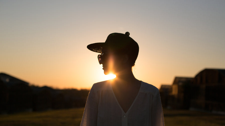 A woman standing in front of the sunset, baseball hat, sunglasses, jewelry