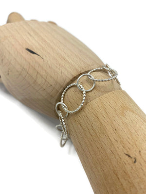a wooden hand has a bracelet wrapped around it.