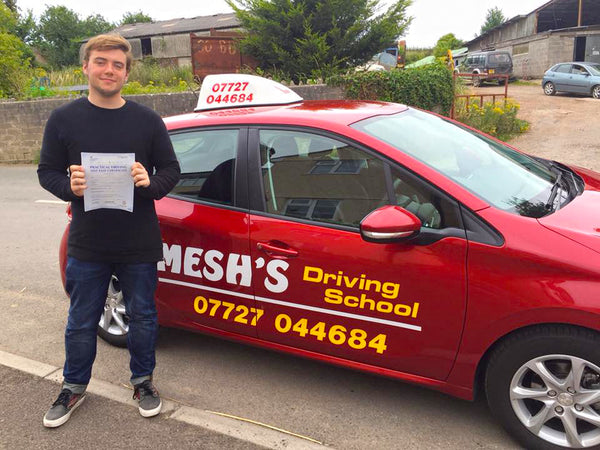 A pupil holding up his driving certificate after passing with Mesh's Driving School