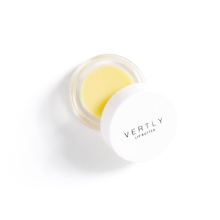 small white chapstick jar with yellow peppermint balm inside