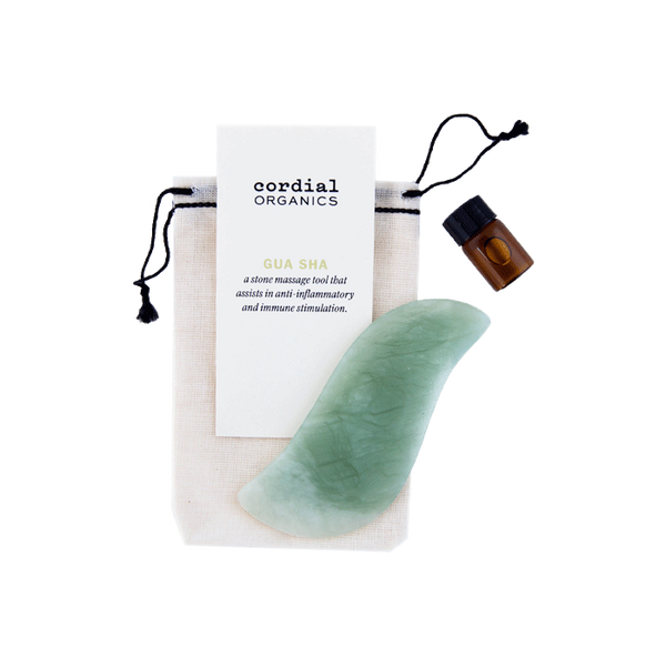 green jade quartz gua sha with small glass oil jar next to hemp bag