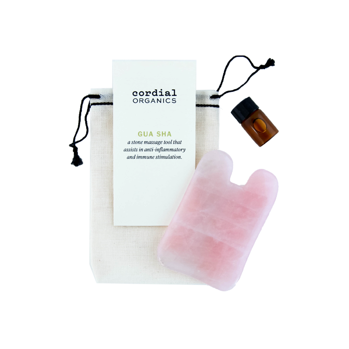 pink rose quartz gua sha with small glass oil jar next to hemp bag