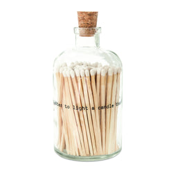 clear glass bottle with cork top containing long matches