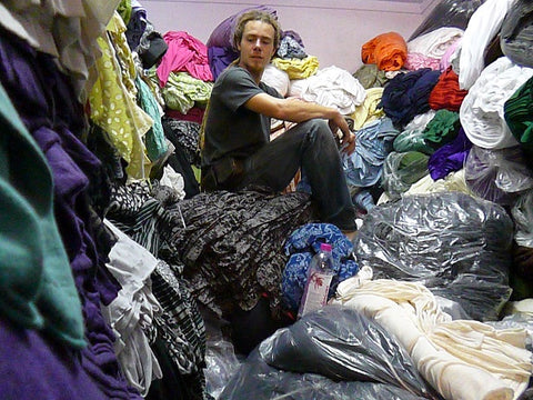 Richard sitting on top of a pile of deadstock fabric | fast fashion pollution | garment Industry Waste | sustainable fashion