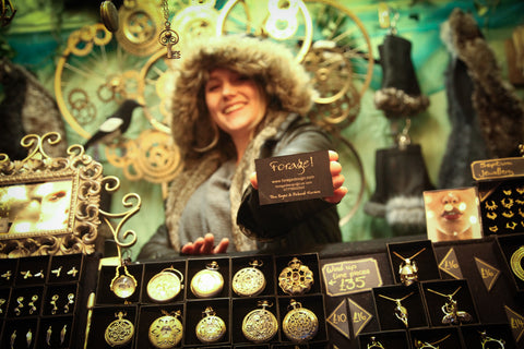 Tina from Forage smiling, with a Forage Design business card at Manchester Christmas Market, pocket watches, bohemian jewellery, hand made silver earrings, ethically sourced jewellery